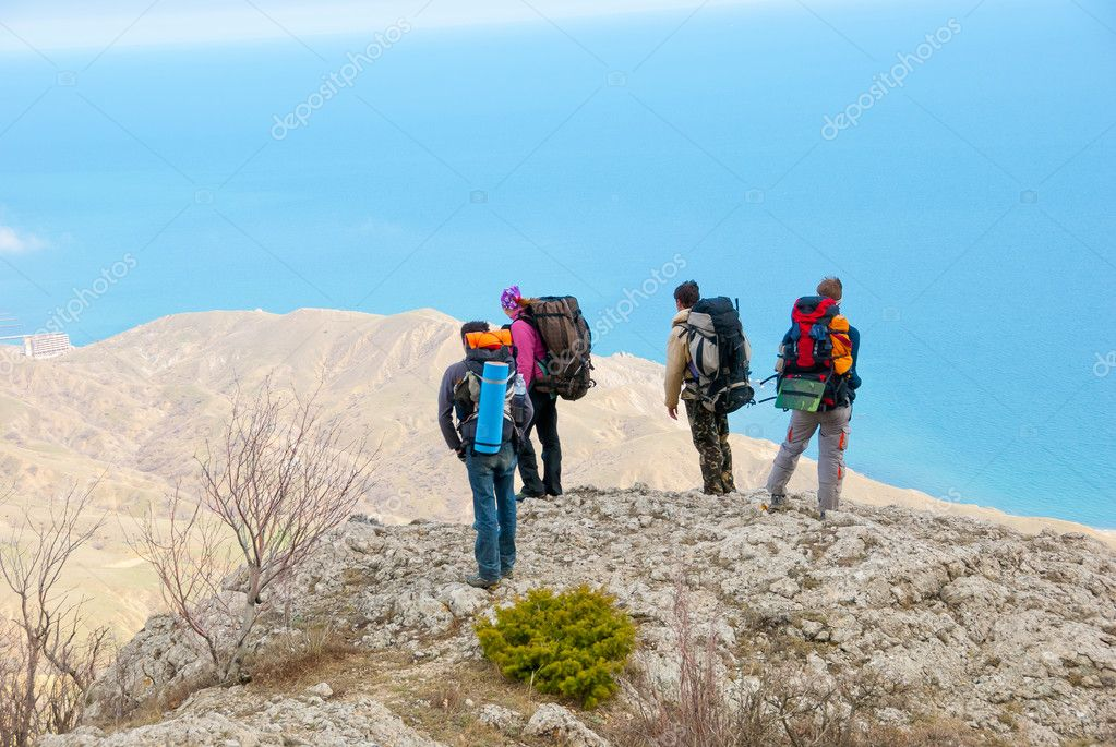Hikers watch the terrain  from the peak of a cliff — Stock Photo #2929288
