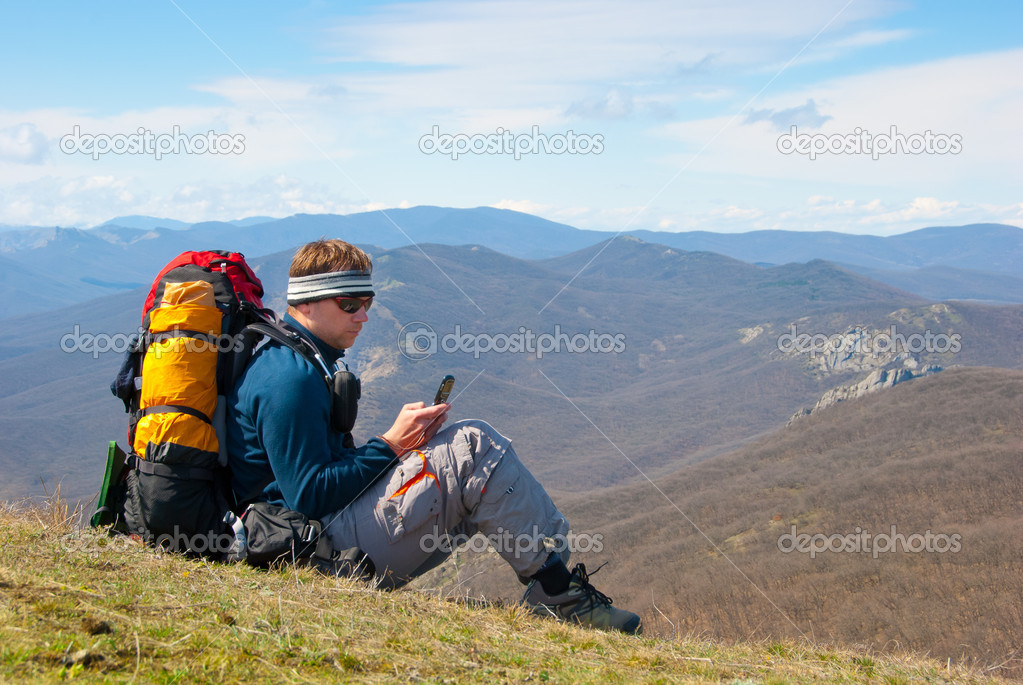 Hiker using mobile device in mountains — Stock Photo #2944878