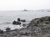 Rocky shoreline and Lighthouse — Stock Photo