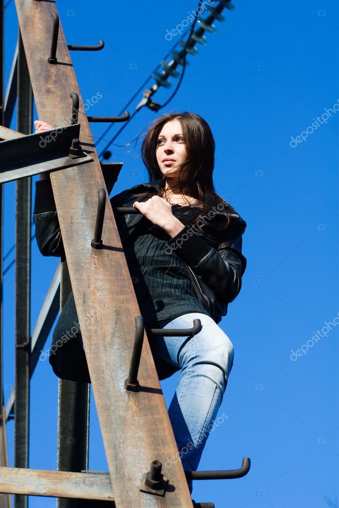 美丽的女人爬上电塔– 图库图片