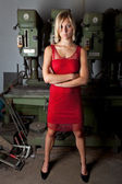 Blonde in a red dress in a garage workshop — Stock Photo
