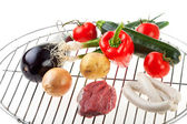 Raw meat, sausages and vegetables on a gridiron — Stock Photo