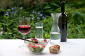 Bowel of salad an rose wine in the garden — Stock Photo