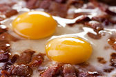 Closeup of two eggs and bacon in a pan — Stock Photo