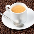 White espresso cup full of coffee sat on coffee beans — Stock Photo #3763116