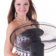 Young pretty female model posing with working fan — Stock Photo