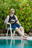 Young man reading nearby the swimming pool — Stock Photo