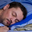 Man with money under his pillow — Stock Photo
