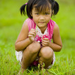 Cute asian girl holding a grasshopper — Stock Photo