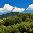 Blue sky view with white clouds over mountains. - Stock Photo