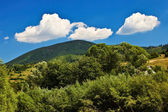 Blue sky view with white clouds over mountains. — Stock Photo
