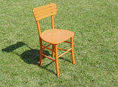 Orange wooden chair on grass — Stock Photo
