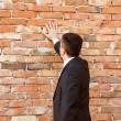 Businessman by brick wall — Foto Stock