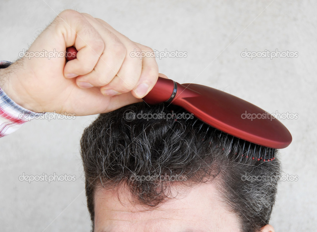 Mature man brushing black greyish hair with red hairbrush — Stock Photo #2847108