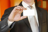 Businessman showing business card — Stock Photo