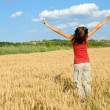 Happy girl jumping in wheat field - Stok fotoraf