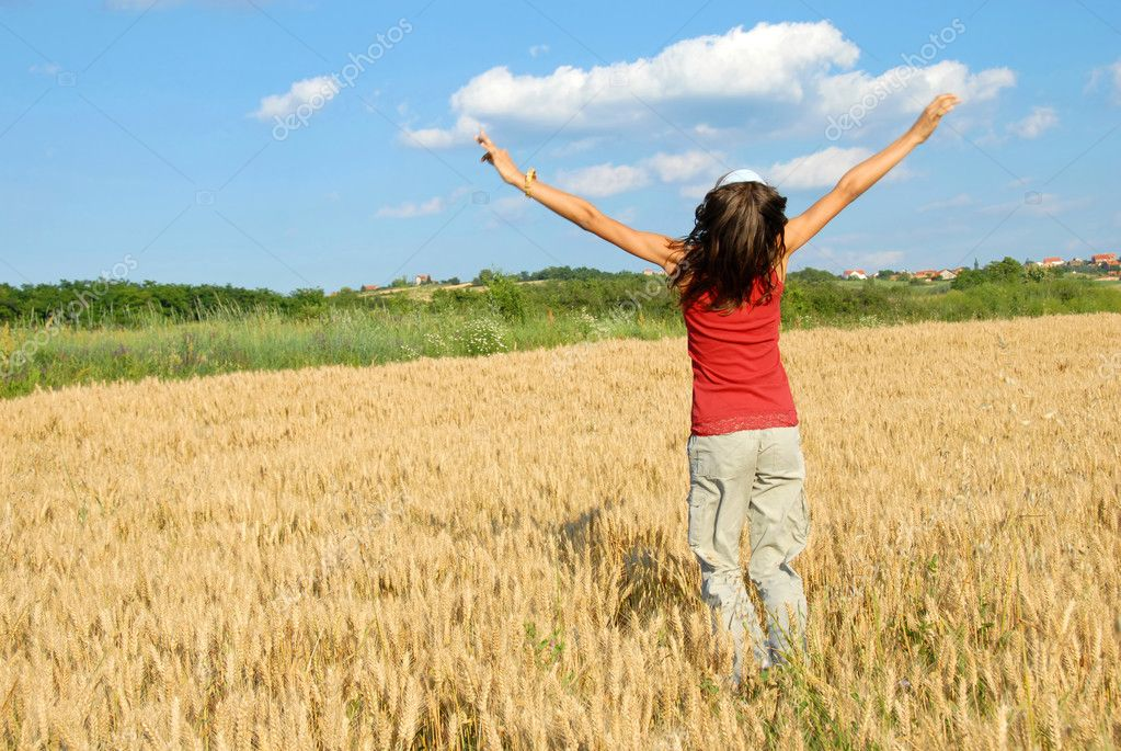 Happy girl jumping in yellow wheat field at scenic rural background — Stock Photo #2901693