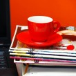 Stock Photo: Red cup on magazines and notebook