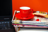 Red cup on magazines and notebook — Stockfoto