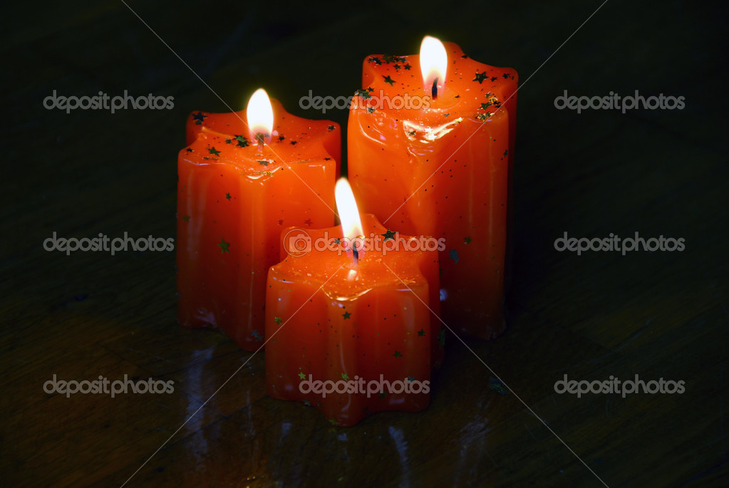 Three orange burning star shape candles on dark wooden background — Stock Photo #3110418