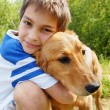 Stock Photo: Boy hugging his dog