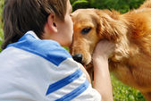 Boy kissing dog — Stock Photo