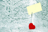 Heart holder with white paper over winter background — Stockfoto