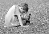 Boy playing in pebble — Stock Photo