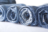 Rotolo jeans denim blu disposti in linea — Foto Stock