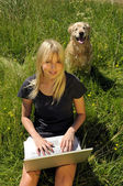 Yong woman with laptop on a meadow — Stock Photo