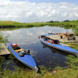 Stock Photo: Canoes on riverbank