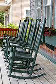 Four green rocking chairs — Stock Photo