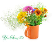 Beautiful summer flowers in an orange mug — Stock Photo