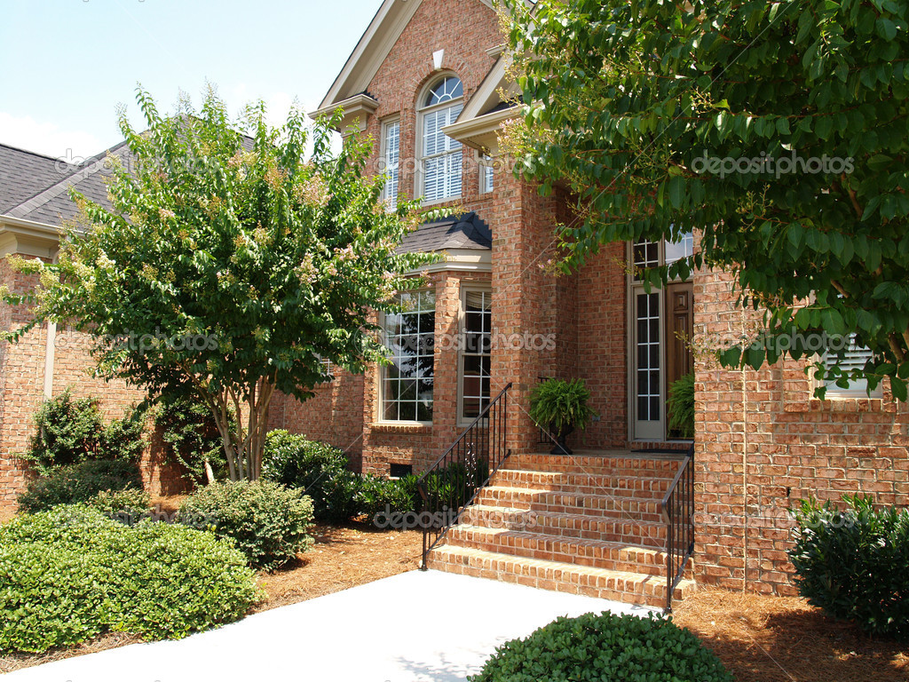 Front of a large brick home with arched windows, beautiful landscaping and wrought iron railings on the steps.  — Photo #3484514