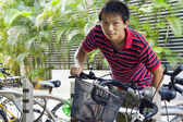 Asia man take bike in bicyle park — Stock Photo