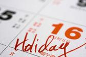 Hand writing holiday on calendar — Stock Photo