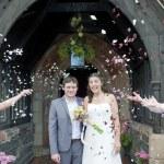 bruid en bruidegom met confetti gegooid — Stockfoto