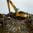 Bulldozwer working on a waste disposal - Stock Photo