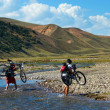 Stock Photo: Two mountain bikers and mountain river