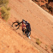 Extreme biker uphill in red canyon — Stock Photo