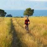 Fiets toeristische op geel veld naast lake — Stockfoto