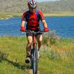 turista di moto in campo verde accanto al lago — Foto Stock