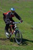 Biker on downhill race — Stock Photo