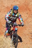 Smiler biker in downhill — Stock Photo