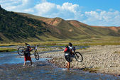 Two mountain bikers and mountain river — Stock Photo