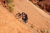 Extreme biker uphill in red canyon — Stockfoto