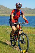 Bike tourist on green field beside lake — Stock Photo