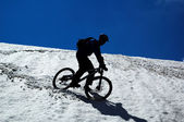 Sky, snow and mountain biker — Stock Photo