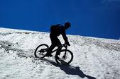 Sky, snow and mountain biker — Stock Photo