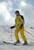Yellow mountain skier on ski resort slope — Stock Photo
